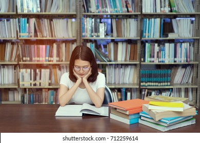 Young student asian girl with glasses reading book serious vision eyesight Hard exam, test and tired stress headache alert worry in classroom library high school university campus, knowledge center.