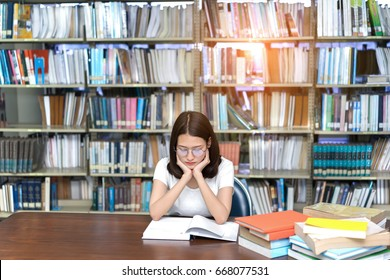 Young student asian girl reading book serious vision eyesight Hard exam, test and tired stress headache alert worry in classroom library high school university campus college and knowledge center.