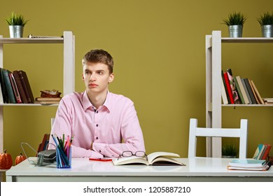 Young student behind the desk dreaming instead of studying . Boy doing homework.