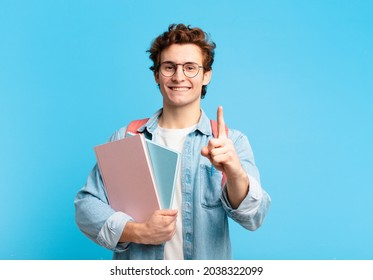 young student boy smiling proudly and confidently making number one pose triumphantly, feeling like a leader