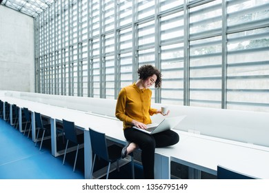 Young student or businesswoman sitting on desk in room in a library or office, using laptop.