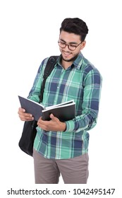 A young student carrying a backpack and holding an open book reading, isolated on a white background.