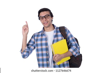 Young student carrying backpack holds yellow book raising a finger got an idea, isolated on a white background.