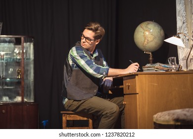 Young student in communist era learning in his apartment  communist housing. studying at home with his earth globe on the old retro desk
