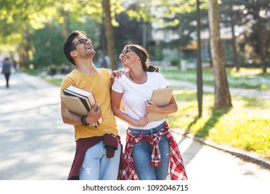 Young student couple going to college class.They walks trough university campus and laughing.