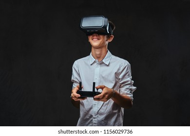 02b08d91d7f6 Young student dressed in a white shirt using virtual reality glasses and  holds a quadcopter control