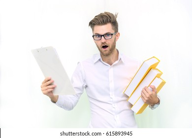 Young student feeling frightened on his exam and holding many textbooks