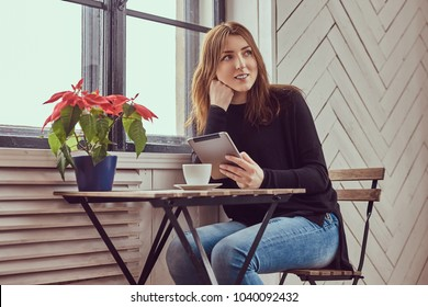 A young student female drinks morning coffee working with a tabl