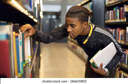 Young student finding reference books in university library. Finding information for his studies.