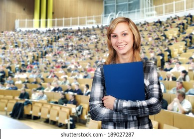 Young student in front of the auditorium in a large lecture hall.