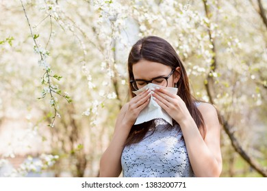 Young student girl hiding her face with white light handkerchief while sneezing. Caucasian female with running nose blows her nose against spring trees. Concept of spring Illness