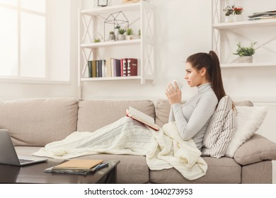 Young student girl reading book. and having coffee. Pensive woman studying at home on beige couch, wrapped up in white blanket, copy space