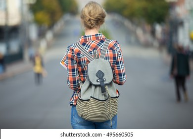 Young student girl walking down the street with a backpack, in the middle of the roadway. Back to school concept photo, back view, horizontal