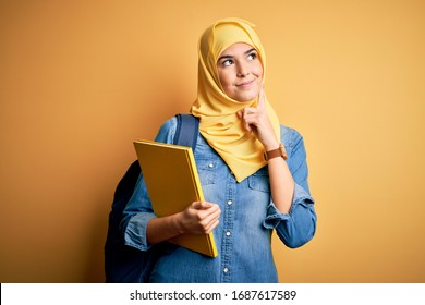 Young student girl wearing muslim hijab and backpack holding book over yellow background serious face thinking about question, very confused idea