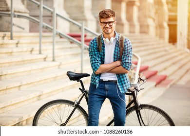 young student with glasses and bike standing on his bike on the street in front of university, looking at camera with confidence and big smile, with folded arms