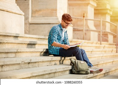 young student with glasses standing on stairs of school or university, looking over his homework