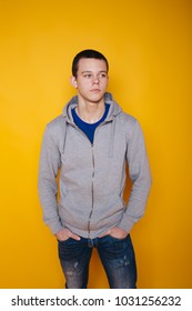 young student guy with short hair and problem skin posing on a paper colored background. emotional portrait of a teenager. street style: blue jeans and a sweatshirt in the spring