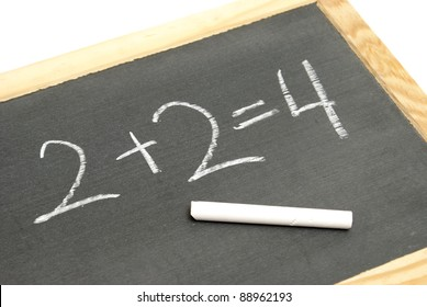 A young student has solved a basic math equation on a chalkboard.