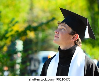 Young student in a hat and gown looking to somewhere against green background