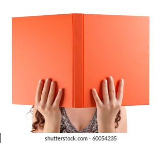 Young student holding book in front of her face.