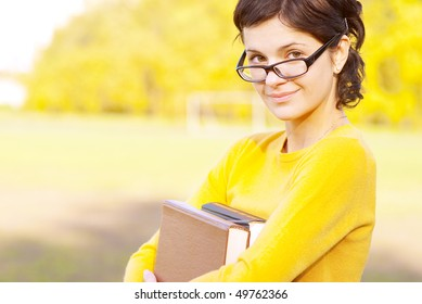 Young student holding books on autumn background.