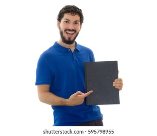 Young student holding and pointing at a black cover notebook. Space for text. Young man wearing blue polo shirt, white background, copy space.