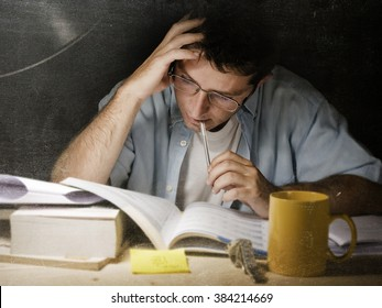 Young student at home desk reading biting pen studying at night with pile of books and coffee cup preparing exam in university education concept in edgy  light set