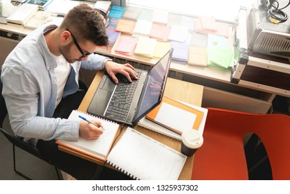 Young student in library, working on laptop