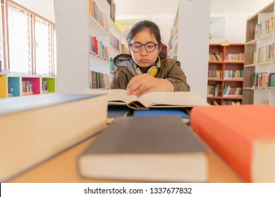 Young student looking at the amount of books she has to read in a classroom