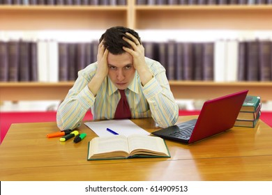 Young student man feel stressed and holding his head. Preparing to entry exams and cramming. Bookshelves on background