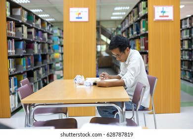 Young student man feel stressed. Preparing to entry exams and cramming. In the library