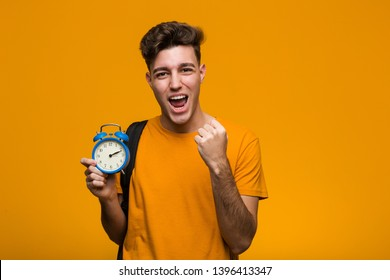 Young student man holding an alarm clock celebrating a victory or success