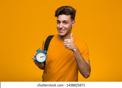 Young student man holding an alarm clock showing victory sign and smiling broadly.