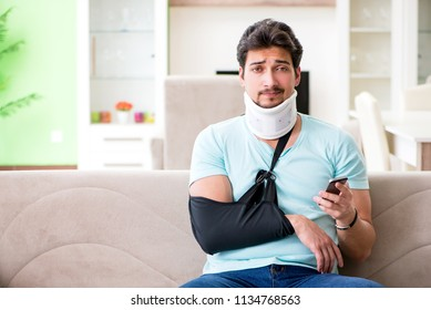 584fa504b068 Young student man with neck and hand injury sitting on the sofa
