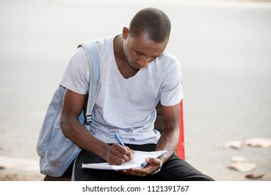young student, a man studying sitting in town after school