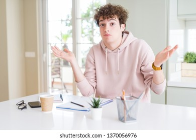 Young student man writing on notebook and studying clueless and confused expression with arms and hands raised. Doubt concept.