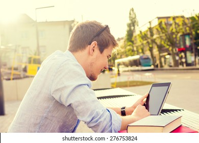Young student men taping on tablet in a city on university bench .Young student  outdoors with tablet.Life style.City