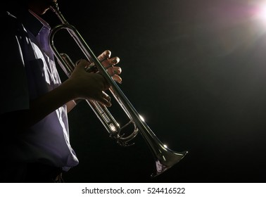 Young student Musician playing the Trumpet with spot light and len flare over dark background on the stage, Musical concept