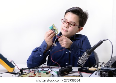Young student performs experiments in electronics and dreams of the future.