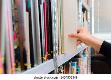 Young student picking a book from the shelf in the library. Preparing for exams, young man searching for or choosing a book in the public library in university