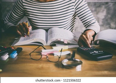 Young student sitting at desk in home studying and reading, doing homework and lesson practice preparing exam to entrance, education concept.