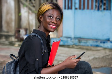 young student sitting with mobile phone watching the camera smiling.
