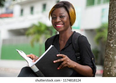 young student sitting in shirt with notebook in hand watching the camera smiling.