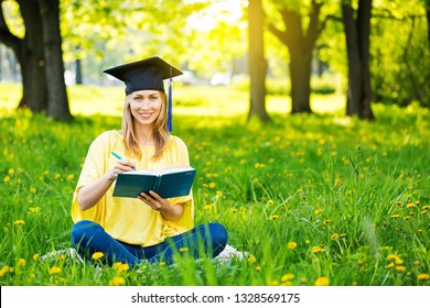 Young student sitting at summer park in graduate cap and writing