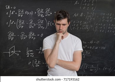Young student is solving math exam. Mathematics formulas on blackboard in background.