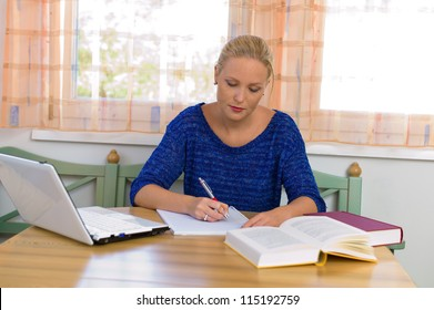 a young student in studying for her degree in her apartment.