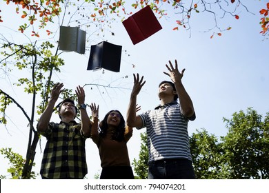 The young student throw  books on the air with friend in the park. Group of teenage students throw book on air celebrating complete academic year. girl joyfully threw books on a sunny day : Education