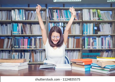 Young student very happy after finished read for examination in library. Success education concept.