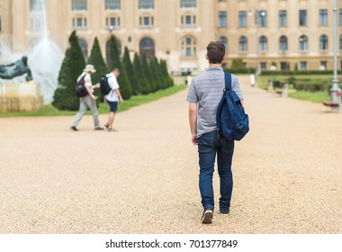 Young student walking to the university. Back view photo