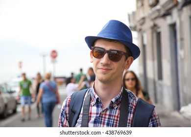 A young student wearing casual clothes and a hat and sunglasses enjoying his vacation in Europe on Amalfi coast in summer.